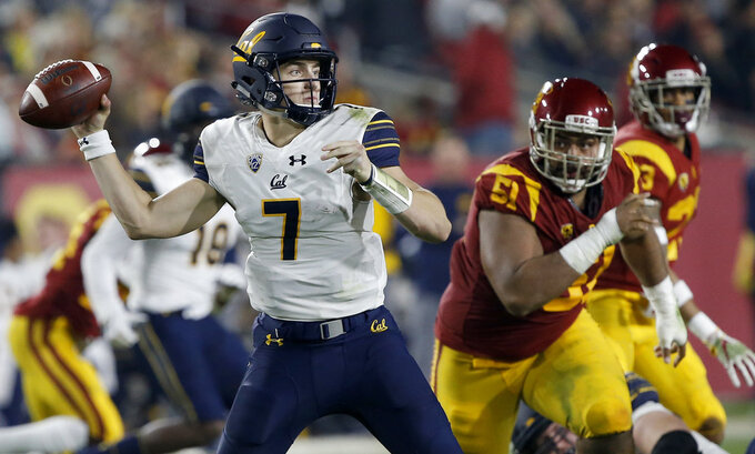 California quarterback Chase Garbers (7) throws a pass under pressure by Southern California defensive lineman Marlon Tuipulotu (51) during the first half of an NCAA college football game in Los Angeles, Saturday, Nov. 10, 2018. (AP Photo/Alex Gallardo)