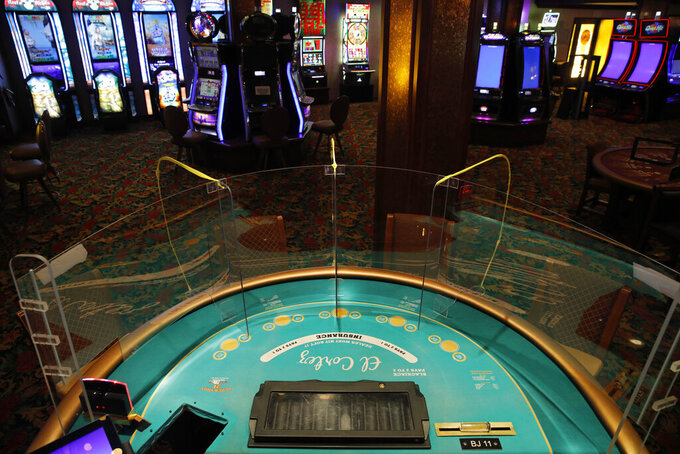 """FILE - In this May 13, 2020, file photo, an acrylic gaming barrier is installed at a gaming table to protect people from the coronavirus at the El Cortez hotel and casino as it remains shuttered due to the coronavirus in Las Vegas. Nevada gambling regulators said Tuesday, May 26, 2020, they may require the state's shuttered casinos to test all """"front line"""" resort workers for COVID-19, enact steps to prevent of the spread of illness and plan to isolate visitors and guests found to have the virus in order to get the OK to emerge from the coronavirus shutdown. (AP Photo/John Locher, File)"""