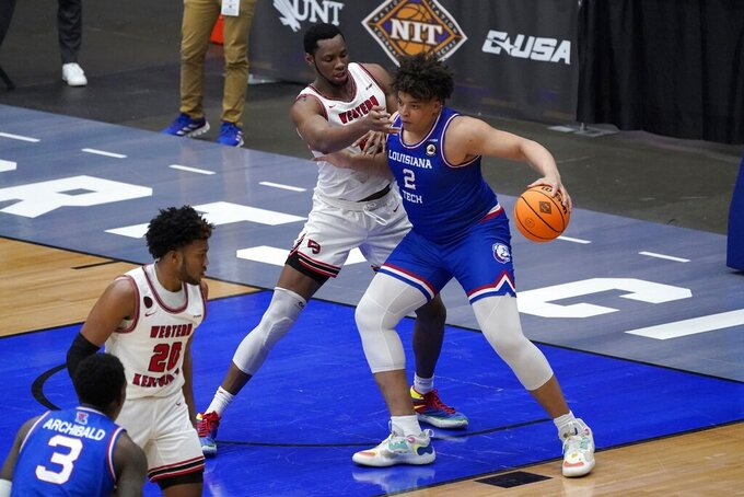 Western Kentucky center Charles Bassey, center left, defends against Louisiana Tech forward Kenneth Lofton Jr. during the second half of an NCAA college basketball game in the quarterfinals of the NIT, Thursday, March 25, 2021, in Frisco, Texas. (AP Photo/Tony Gutierrez)