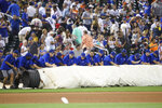 Members of the grounds crew roll out the tarp during a rain delay in the sixth inning of a baseball game between the New York Mets and the Cleveland Indians, Thursday, Aug. 22, 2019, in New York. (AP Photo/Mary Altaffer)
