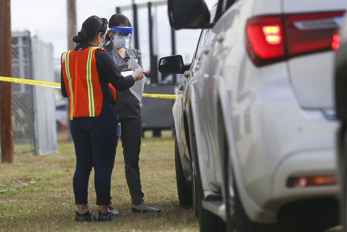 Staff help register and process those waiting in their vehicles in the line for non-ambulatory people to be vaccinated Tuesday, Jan. 5, 2021, at the COVID-19 vaccination clinic on the Rio Grande Valley Livestock Show grounds in Mercedes, Texas. (Denise Cathey/The Brownsville Herald via AP)
