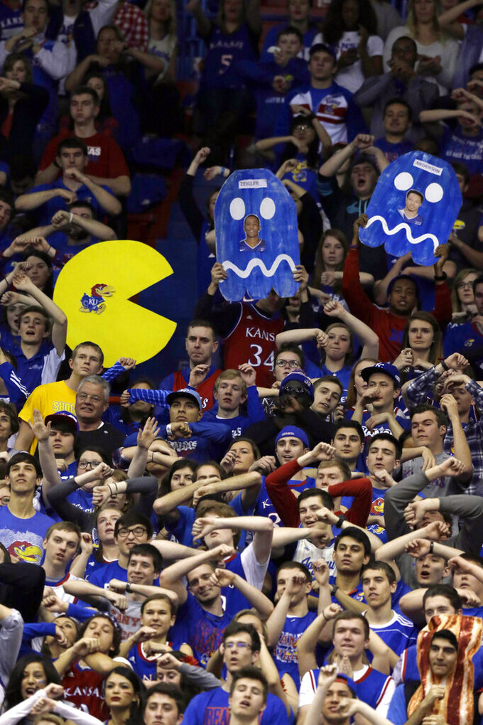 "FILE- In this Feb. 21, 2015, file photo, Kansas fans cheer during the first half of an NCAA college basketball game against TCU at Allen Fieldhouse in Lawrence, Kan. As the season begins in earnest this week, with a full slate of Division I games Wednesday, fans will notice the absence of traditions such as the Silent Night game across the college basketball landscape. The population of Krzyzewskiville at Duke will be zero, the Oakland Zoo at Pittsburgh a bit more tame. The Orange Crush at Illinois will be less intimidating and the ghost-like sound of ""Rock Chalk Jayhawk"" at Kansas will be merely the echoes from thousands of previous wins.  (AP Photo/Orlin Wagner, File)"