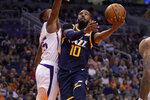 Utah Jazz guard Mike Conley (10) shoots around Phoenix Suns forward Mikal Bridges during the first half of an NBA basketball game, Monday, Oct. 28, 2019, in Phoenix. (AP Photo/Matt York)