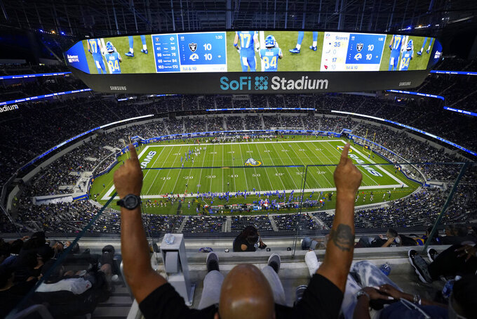 A fan cheers from the upper deck at SoFi Stadium during the second half of a preseason NFL football game between the Los Angeles Rams and the Las Vegas Raiders on Saturday, Aug. 21, 2021, in Inglewood, Calif. (AP Photo/Jae C. Hong)