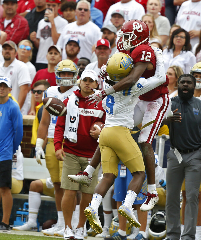 UCLA defensive back Elijah Gates (9) interferes with Oklahoma wide receiver A.D. Miller (12) as Miller attempts to catch a pass in the second half of an NCAA college football game in Norman, Okla., Saturday, Sept. 8, 2018. Oklahoma won 49-21. (AP Photo/Sue Ogrocki)