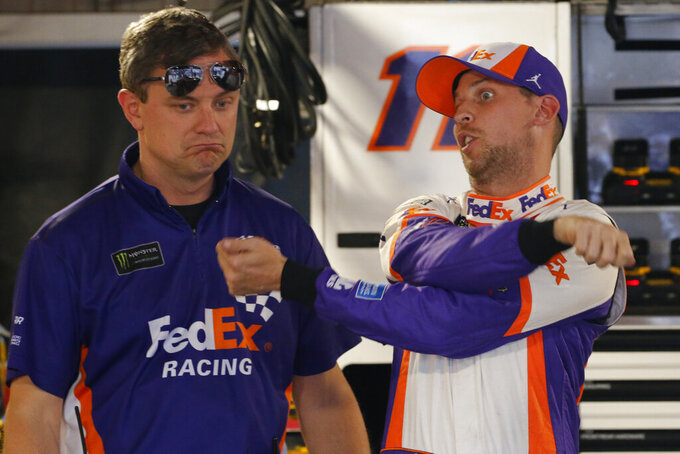 Denny Hamlin, right, talks to his crew chief, Chris Gabehart, after qualifying for the NASCAR Cup Series race at Martinsville Speedway in Martinsville, Va., Saturday, Oct. 26, 2019. Hamlin won the pole. (AP Photo/Steve Helber)