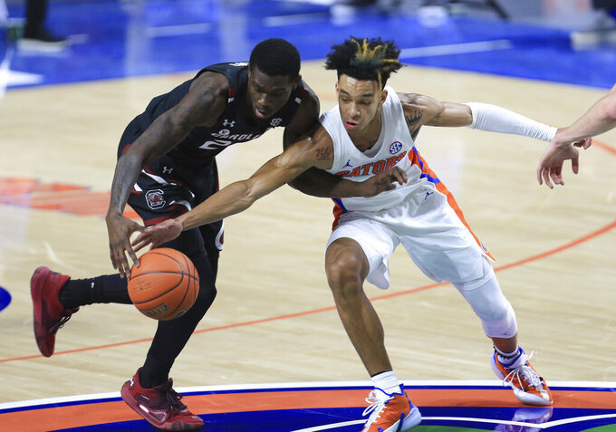 Florida guard Tre Mann, right, steals the ball from South Carolina forward Keyshawn Bryant during the first half of an NCAA college basketball game Wednesday, Feb. 3, 2021, in Gainesville, Fla. (AP Photo/Matt Stamey)