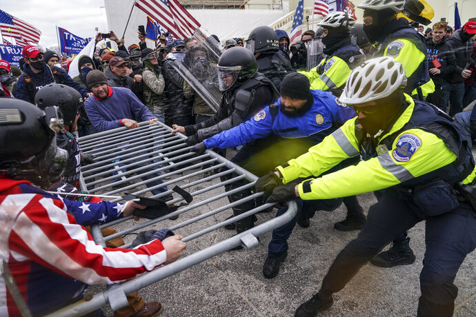 FILE - In this Jan. 6, 2021, file photo, Trump supporters try to break through a police barrier at the Capitol in Washington. There is increasing concern for the safety of journalists covering protests at state capitals across the U.S., and in Washington. Packing a gas mask and helmet has become the new normal. It's starting to look, just a bit, like what foreign correspondents face in the world's conflict zones. (AP Photo/John Minchillo, File)