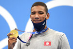 Ahmed Hafnaoui, of Tunisia, poses with his gold medal after winning final of the men's 400-meter freestyle at the 2020 Summer Olympics, Sunday, July 25, 2021, in Tokyo, Japan. (AP Photo/Matthias Schrader)