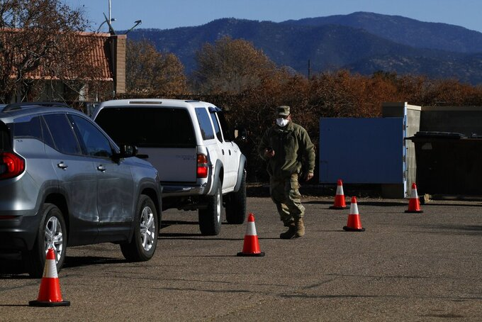 An Army National Guard soldier processes a line of cars full of people getting COVID-19 tests on Wednesday, Dec. 23, 2020, in Santa Fe, New Mexico. (AP Photo/Cedar Attanasio)