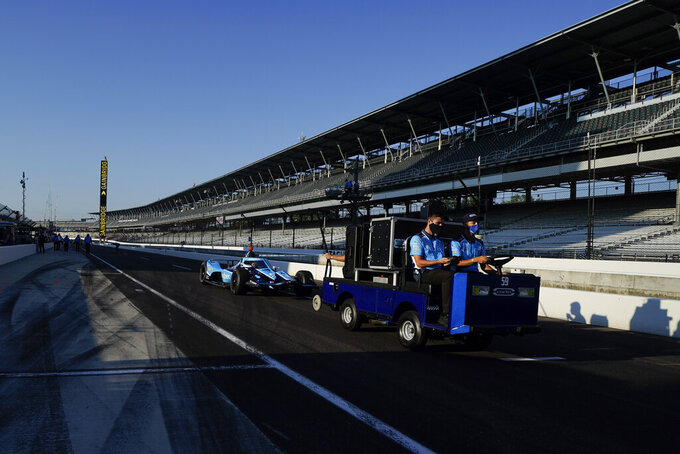 The car of Max Chilton, of England, is towed along pit lane before a practice session for the Indianapolis 500 auto race at Indianapolis Motor Speedway, Saturday, Aug. 15, 2020, in Indianapolis. (AP Photo/Darron Cummings)