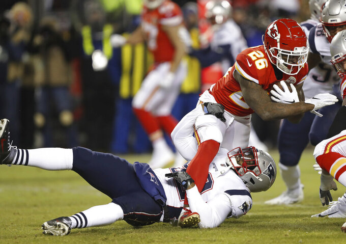 Kansas City Chiefs running back Damien Williams (26) is tackled by New England Patriots outside linebacker Elandon Roberts (52) during the first half of the AFC Championship NFL football game, Sunday, Jan. 20, 2019, in Kansas City, Mo. (AP Photo/Charlie Neibergall)