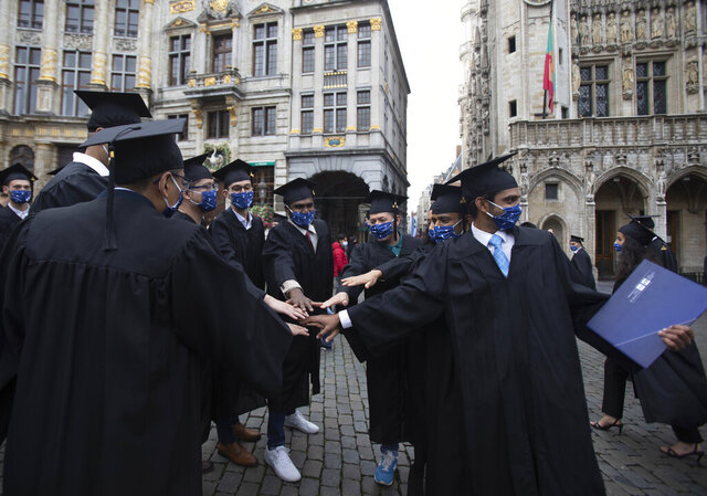 Engineering graduates of the Universite Libre De Bruxelles, cheer after a graduation ceremony at the Grand Place in Brussels, Wednesday, Sept. 30, 2020. Many of these students were supposed to graduate in June, but with exams cancelled and COVID-19 regulations in place many students were unable to manage that in time. Pandemic restrictions limited the guest invitations to only 2 persons for each graduate. (AP Photo/Virginia Mayo)