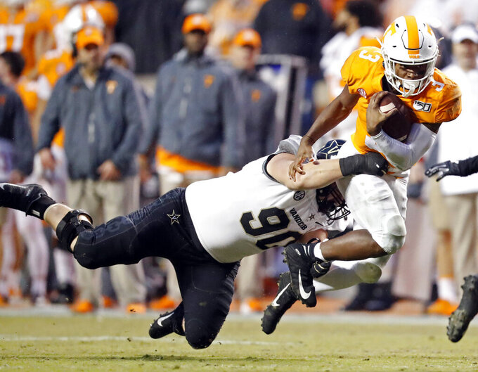 Tennessee running back Eric Gray (3) runs for yardage as he's tackled by Vanderbilt defensive lineman Cameron Tidd (90) in the first half of an NCAA college football game Saturday, Nov. 30, 2019, in Knoxville, Tenn. (AP Photo/Wade Payne)