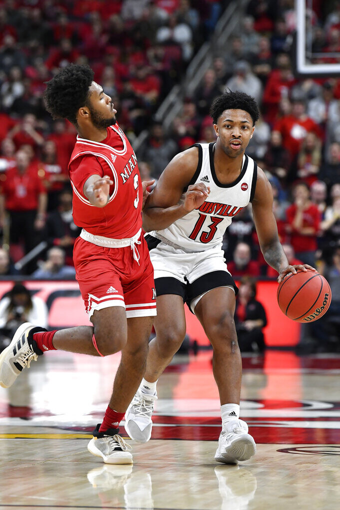 Louisville guard David Johnson (13) is defended by Miami (Ohio) guard Dae Dae Grant (3) during the second half of an NCAA college basketball game in Louisville, Ky., Wednesday, Dec. 18, 2019. Louisville won 70-46. (AP Photo/Timothy D. Easley)