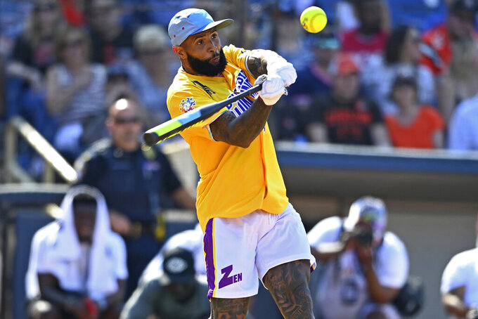 Cleveland Browns wide receiver Odell Beckham Jr. swings during the Jarvis Landry Celebrity Softball game Saturday, June 12, 2021, in Eastlake, Ohio. (AP Photo/David Dermer)