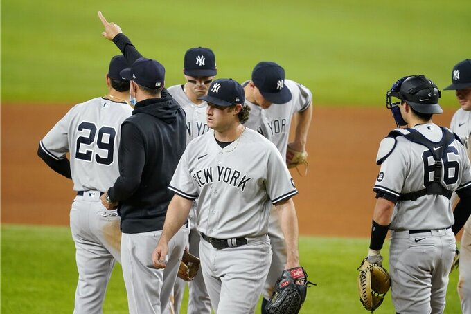 New York Yankees manager Aaron Boone gestures to the bullpen after taking the ball from starting pitcher Gerrit Cole, center, in the sixth inning of a baseball game against the Texas Rangers in Arlington, Texas, Monday, May 17, 2021. (AP Photo/Tony Gutierrez)