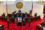 Caroline Basnight, left, and sister Vicki Basnight, unveil a portrait of their father, former Senate President Pro Tempore Marc Basnight during a ceremony on Tuesday, Sept.  21, 2021 at the General Assembly in Raleigh, N.C. Basnight died in December 2020 and served 13 terms in the North Carolina Senate. (Robert Willett/The News & Observer via AP)