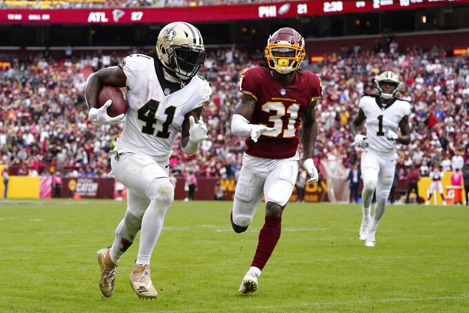New Orleans Saints running back Alvin Kamara, left, rushes past Washington Football Team free safety Kamren Curl for a touchdown in the second half of an NFL football game, Sunday, Oct. 10, 2021, in Landover, Md. (AP Photo/Alex Brandon)