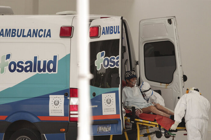 A patientinfected with the new coronavirus is transferred from an ambulance onto a stretcher at the National Hospital emergency entrance in San Salvador, El Salvador, Friday, Aug. 7, 2020. For months, the strictest measures confronting the COVID-19 pandemic in Latin America seemed to keep infections in check, in El Salvador, but a gradual reopening combined with a political stalemate has seen infections increase nearly fourfold. (AP Photo/Salvador Melendez)