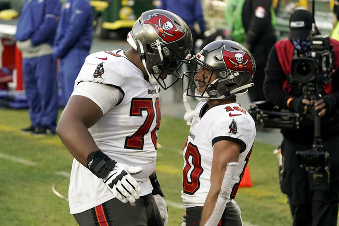 Tampa Bay Buccaneers' Scott Miller (10) celebrates his 39-yard touchdown reception with Tristan Wirfs against the Green Bay Packers during the first half of the NFC championship NFL football game in Green Bay, Wis., Sunday, Jan. 24, 2021. (AP Photo/Morry Gash)