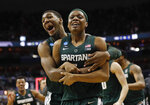 Michigan State guard Cassius Winston (5) is hugged by teammate forward Aaron Henry (11) after defeating Duke in an NCAA men's East Regional final college basketball game in Washington, Sunday, March 31, 2019. Michigan State won 68-67. (AP Photo/Patrick Semansky)
