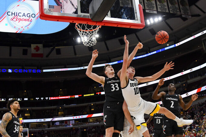 Iowa guard Joe Wieskamp (10) and Cincinnati center Chris Vogt (33) and guard Keith Williams (2) look for a rebound during the first half of an NCAA college basketball game Saturday, Dec. 21, 2019, in Chicago. (AP Photo/Matt Marton)