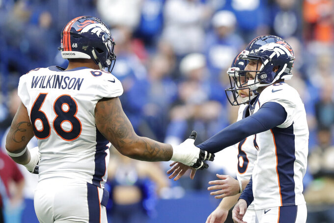 Denver Broncos kicker Brandon McManus (8) is congratulated by Elijah Wilkinson (68) after McManus kicked a field goal during the first half of an NFL football game against the Indianapolis Colts, Sunday, Oct. 27, 2019, in Indianapolis. (AP Photo/Michael Conroy)