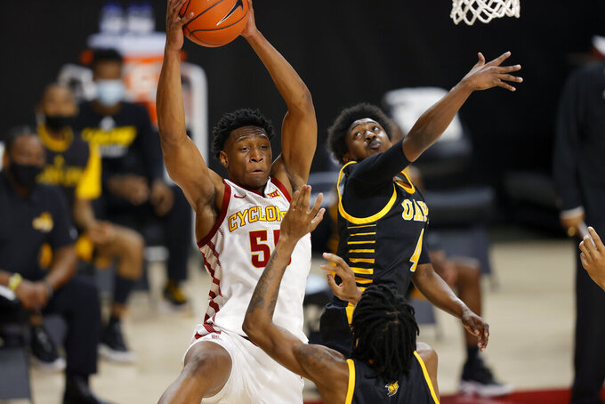 Iowa State guard Darlinstone Dubar, top left, looks to pass under the basket as Arkansas-Pine Bluff guards Dequan Morris, center, and Joshuwa Johnson, right, defend during the first half of an NCAA college basketball game, Sunday, Nov. 29, 2020, in Ames, Iowa. (AP Photo/Matthew Putney)