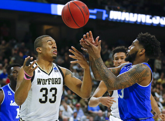 Wofford's Cameron Jackson (33) and Seton Hall's Myles Powell, right, go after a loose ball during the first half of a first-round game in the NCAA men's college basketball tournament in Jacksonville, Fla., Thursday, March 21, 2019. (AP Photo/Stephen B. Morton)