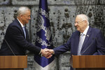Israeli President Reuven Rivlin, right, shakes hands with Blue and White Party leader Benny Gantz iafter he gave Gantz a mandate to form new government in Jerusalem, Wednesday, Oct. 23, 2019. (AP Photo/Sebastian Scheiner)