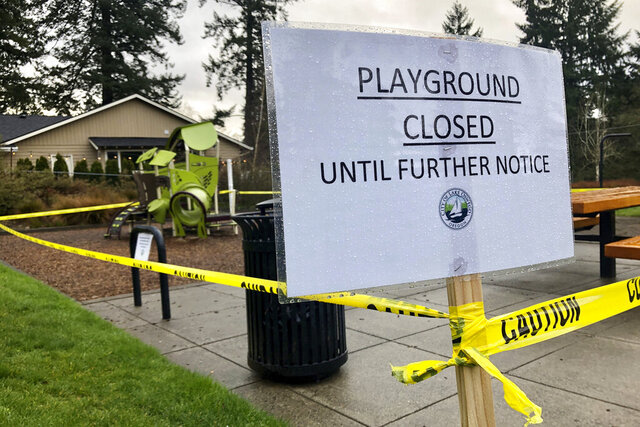 Police caution tape surrounds a playground in Lake Oswego, Ore., on Tuesday, March 24, 2020, the day after Gov. Kate Brown issued a statewide stay-at-home order that closed many businesses, as well as all playgrounds, basketball courts and sport courts. (AP Photo/Gillian Flaccus)