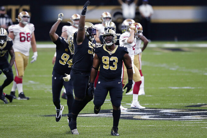 New Orleans Saints defensive tackle Malcolm Roach, center, defensive tackle David Onyemata (93) and defensive end Cameron Jordan (94) celebrate a defensive stop on fourth down in the first half of an NFL football game against the San Francisco 49ers in New Orleans, Sunday, Nov. 15, 2020. (AP Photo/Butch Dill)
