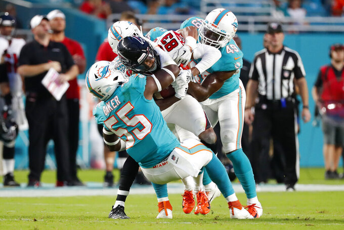 Atlanta Falcons wide receiver Russell Gage (83) is tackled by Miami Dolphins outside linebacker Jerome Baker (55) and linebacker Sam Eguavoen (49) during the first half of a preseason NFL football game Thursday, Aug. 8, 2019, in Miami Gardens, Fla. (AP Photo/Wilfredo Lee)