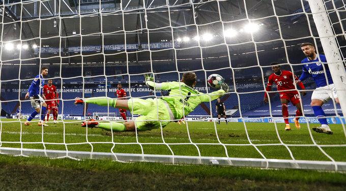 Bayern's goalkeeper Manuel Neuer saves a ball from Schalke's Mathew Hoppe during the German Bundesliga soccer match between FC Schalke 04 and Bayern Munich in Gelsenkirchen, Germany, Sunday, Jan. 24, 2021. (AP Photo/Martin Meissner, Pool)
