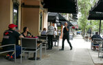Customers enjoy sidewalk dinning in Orlando, Fla, Monday, May 18, 2020. Fitness centres were allowed to reopen in parts of Florida today and restaurants could open at 50 percent capacity.(AP Photo/John Raoux)