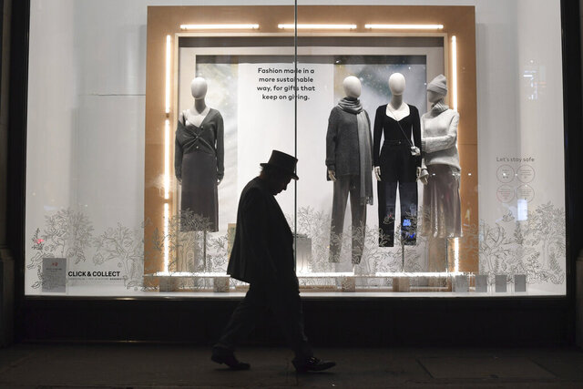 A man walks past a closed shop on Regent Street in central in London, Sunday, Dec. 20, 2020.  Millions of people in England have learned they must cancel their Christmas get-togethers and holiday shopping trips. British Prime Minister Boris Johnson said Saturday that holiday gatherings can't go ahead and non-essential shops must close in London and much of southern England. Johnson imposed a new, higher level of coronavirus restrictions to curb sharply spreading infections in the capital and other areas.  (Stefan Rousseau/PA via AP)