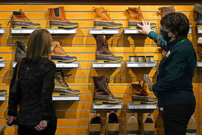 A salesperson helps a customer shopping for Bean Boots at the L.L. Bean flagship retail store, Thursday, March 18, 2021, in Freeport, Maine.  Maine-based retailer L.L. Bean saw the best sales in nearly a decade during pandemic. Officials say the Freeport-based retailer started its fiscal year with store closings and worries about survival but the company weathered the turbulent times to revenue growth of 5%.  (AP Photo/Robert F. Bukaty)