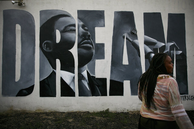 Lorinda Lacy, 45, stands outside her party store painted with a mural depicting Martin Luther King Jr. in the Watts neighborhood of Los Angeles, Tuesday, June 30, 2020. Lacy moved out of Watts 20 years ago because she didn't want her daughters to grow up with the trauma she experienced as a girl. She said she eventually became