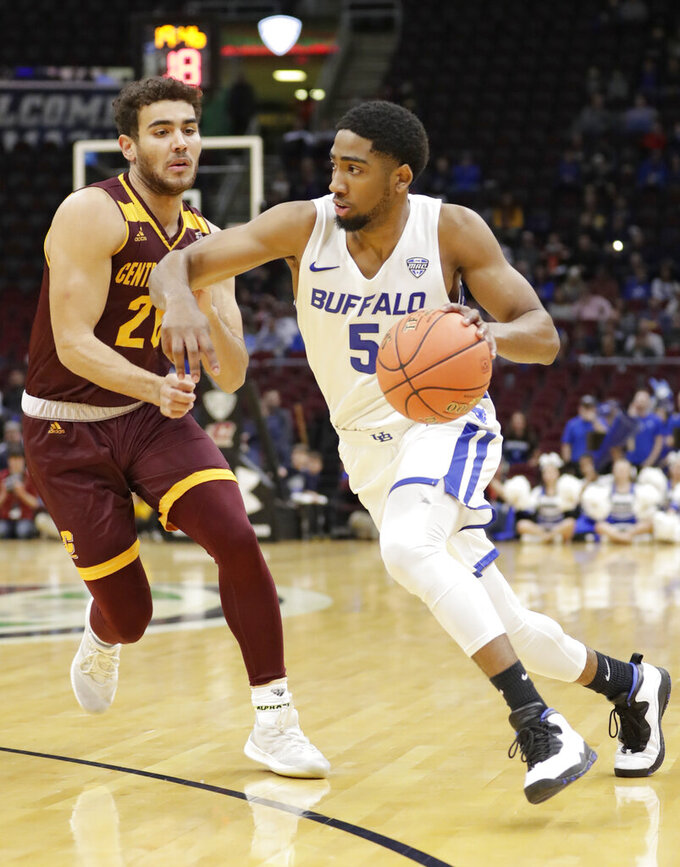 Buffalo's CJ Massinburg (5) drives past Central Michigan's Kevin McKay (20) during the first half of an NCAA college basketball game in the semifinals of the Mid-American Conference men's tournament Friday, March 15, 2019, in Cleveland. (AP Photo/Tony Dejak)