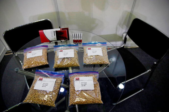FILE - In this April 12, 2018 file photo, packets of raw soybeans are placed on a table at a U.S. soybean company's booth at the international soybean exhibition in Shanghai, China. With the threat of tariffs and counter-tariffs between Washington and Beijing looming, Chinese buyers are canceling orders for U.S. soybeans, a trend that could deal a blow to American farmers if it continues. At the same time, farmers in China are being encouraged to plant more soy, apparently to help make up for any shortfall from the United States. (AP Photo/Andy Wong, File)