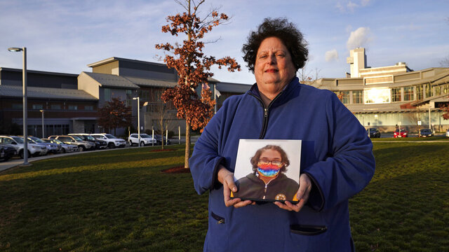 Laura Dilts, of Barre, Mass., holds a photograph of her 16-year-old son outside the Worcester Recovery Center, where he is a resident patient receiving assistance for his mental health, Monday, Nov. 23, 2020, in Worcester, Mass. The coronavirus pandemic has led to rising emergency room visits and longer waits for U.S. children and teens facing mental health issues. (AP Photo/Charles Krupa)