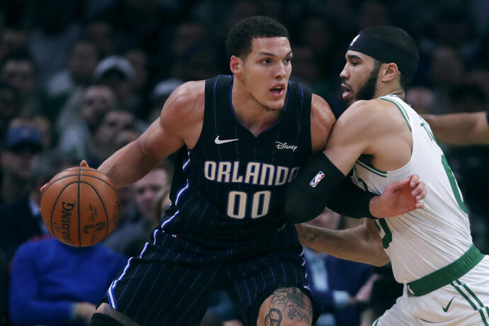 Boston Celtics forward Jayson Tatum, right, tries to stop Orlando Magic forward Aaron Gordon (00) during the second quarter of an NBA basketball game in Boston, Wednesday, Feb. 5, 2020. (AP Photo/Charles Krupa)