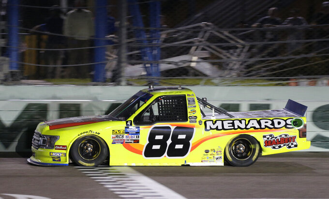 Matt Crafton crosses the finish line, and wins the NASCAR Truck Series auto racing season championship Friday, Nov. 15, 2019, at Homestead-Miami Speedway in Homestead, Fla. (AP Photo/Terry Renna)