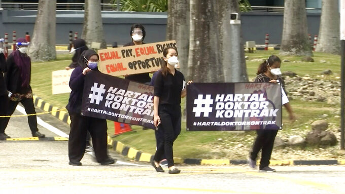 """In this image from video, doctors hold banners in Malay that read """"Contract Doctors Walkout"""" while participating  in a walkout held at the Sungai Buloh Hospital in Selangor, Malaysia Monday, July 26, 2021. Scores of doctors staged walkouts from Malaysian government hospitals on Monday, demanding fairer treatment for more than 20,000 contract doctors who play a key role in the fight against the worsening coronavirus pandemic. (AP Photo)"""