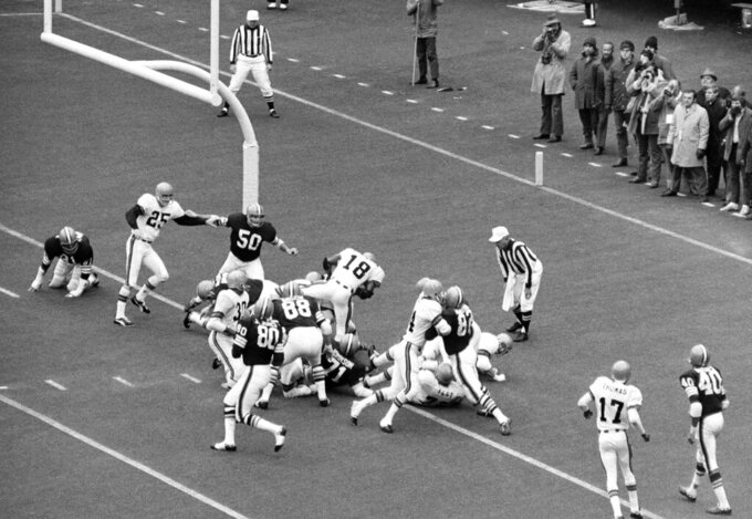 FILE - In this Nov. 15, 1970, file photo, Cincinnati Bengals' Paul Robinson (18) scores the game-winning touchdown from the one-yard-line in the first half of a football game against the Cleveland Browns in Cincinnati. Others shown are Bengals' Jess Phillips (30) and Browns' Joe Jones (80), Jim Houston (82), Ron Snidow (88), Walter Johnson (71) and John Garlington (50). The Cincinnati Bengals' 14-10 victory over the Cleveland Browns on a snowy, November afternoon in 1970 put Brown's new team on equal footing with his old one and made Ohio truly a two-team pro football state. (AP Photo/GS, File)