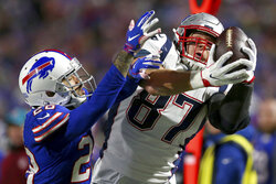 FILE - In this Oct. 29, 2018, file photo, New England Patriots tight end Rob Gronkowski, right, makes a catch next to Buffalo Bills defensive back Phillip Gaines during the second half of an NFL football game in Orchard Park, N.Y. Gronkowski, the retired Patriots tight end, is set to host WrestleMania in April from WWE's performance center. (AP Photo/Jeffrey T. Barnes, File)