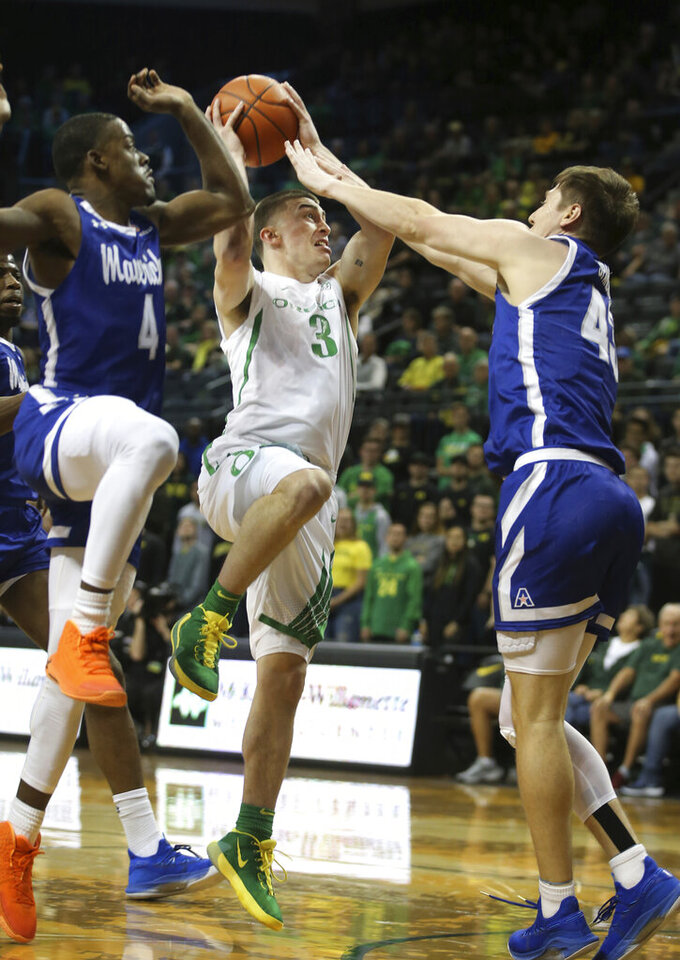 Oregon's Payton Pritchard, center, goes up for a basket against Texas Arlington's David Azore, left, and Coleman Sparling the first half of an NCAA college basketball game in Eugene, Ore., Sunday, Nov. 17, 2019. (AP Photo/Chris Pietsch)