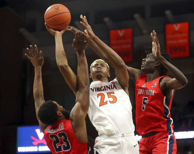 Virginia forward Mamadi Diakite (25) shoots between Stony Brook guard Andrew Garcia (23) and forward Mouhamadou Gueye (5) during an NCAA college basketball game in Charlottesville, Va., Wednesday, Dec. 18, 2019. Virginia won 56-44. (AP Photo/Andrew Shurtleff)