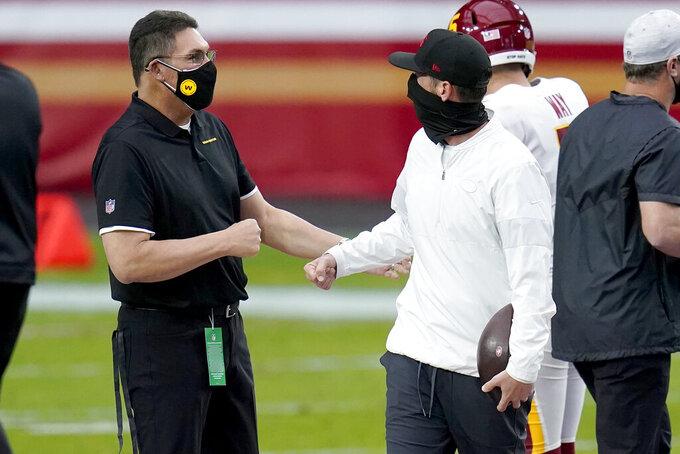 Washington Football Team head coach Ron Rivera, left, greets San Francisco 49ers head coach Kyle Shanahan prior to an NFL football game, Sunday, Dec. 13, 2020, in Glendale, Ariz. (AP Photo/Ross D. Franklin)